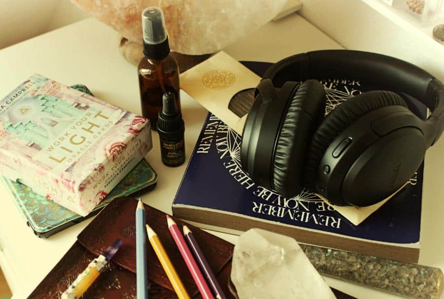 items from my self care kit including spray bottle, headphones, books, kindle, pencils, journal and crystals